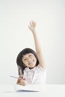 元気よく手を上げる笑顔の小学生女子