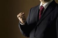 拳を握るスーツの男性