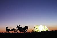ノートPCを使う男性とキャンプのテント
