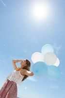 海岸で風船を持っている笑顔の日本人女性