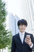 スマートフォンを見る笑顔の日本人ビジネスマン