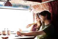キャンピングカーでトランプをする若いカップル