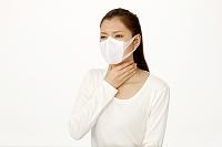 マスクをして喉を手で触る女性
