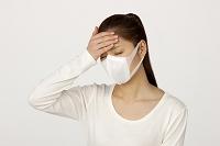 マスクをして額に手をあてる女性