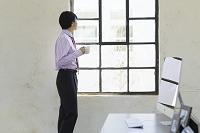 窓辺でリフレッシュする日本人ビジネスマン