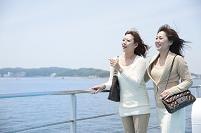 フェリーのデッキで海を見る母と娘
