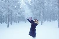 森の中で雪を舞い上げる女性