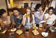 居酒屋で食事する日本人と外国人の若者