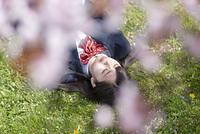 芝生に寝転ぶ女子学生