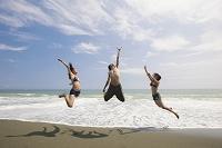 海辺でジャンプする若者