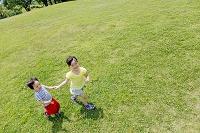 公園を手を繋いで歩く姉と弟
