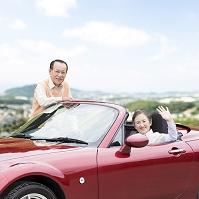 オープンカーに乗る日本人のシニア夫婦