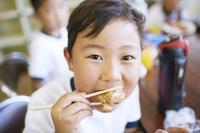 教室で昼食をとる小学生の男の子