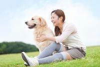 芝生に座っている日本人女性と犬