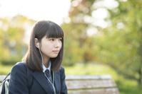 ベンチで音楽を聴く女子学生