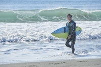 サーフボードを持つ日本人男性