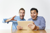タブレットを見て驚く日本人と外国人男性