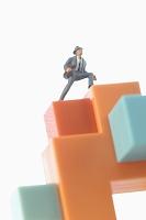 ブロックの上に立つビジネス男性の人形