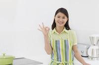 キッチンでOKポーズをする日本人女性