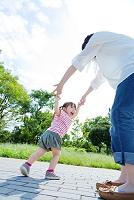 公園で手をとって遊ぶ母親と娘