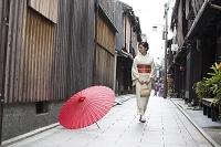 祇園の通りに立つ着物の日本人女性