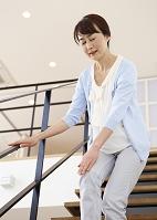 階段で膝を押さえるシニアの日本人女性