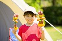 バーベキューの串を持つ日本人の男の子
