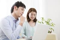 PCを見ながら談笑する夫婦