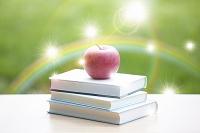 虹と勉強机に置かれた本とリンゴ