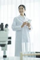 スマートフォンを使う白衣を着た女性