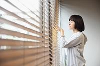 窓辺から遠くを見る若い日本人女性