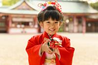 獅子舞のおもちゃを持つ晴れ着の女の子