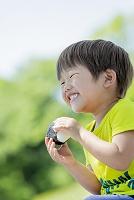 公園でおにぎりを食べる日本人の男の子