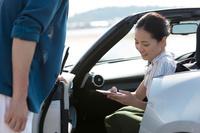 オープンカーに座ってスマートフォンを見ている女性