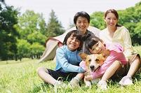 キャンプをしている家族と犬