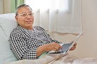 ベッドでパソコンを使うシニア男性患者