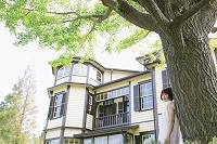 家と木に寄りかかる女性
