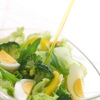 ドレッシングをそそぐ野菜サラダ