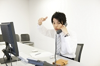 電話をしながら手招きをするビジネスマン