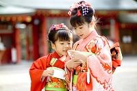 お年玉を見る着物の姉妹 神社にて