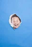 破れた紙の穴から覗く男の子の笑顔
