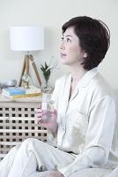 ベッドでコップを持つミドル日本人女性