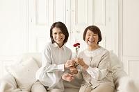 花をプレゼントする娘とシニア日本人女性