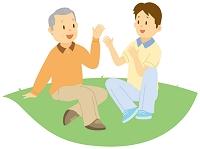 介護士と芝生に座って話す老人男性
