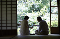縁側で日本酒を飲む日本人シニア夫婦