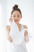 タオルで顔を拭く日本人女性