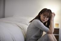 寝室でくつろぐ眼鏡の日本人女性
