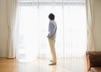 リビングの窓際で通話するミドルの日本人男性