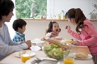 ダイニングテーブルで食事をする家族