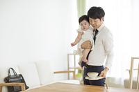 子育てイメージ 出勤前の日本人の若い父親と女の子の赤ちゃん